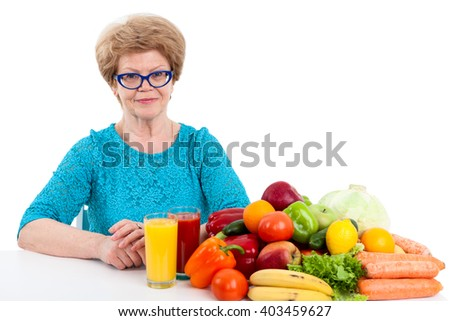 An elder Caucasian woman with tomato and orange juice in glasses sits at table with fruits and vegetables, isolated on white background - stock photo