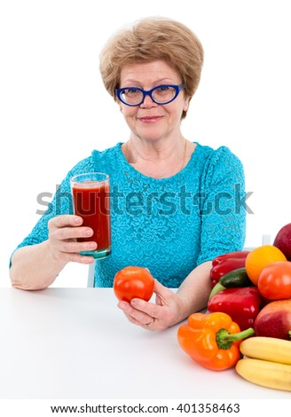 An elder woman holding glass of red juice and tomato in hands, fresh fruits and vegetables are on table, isolated on white background - stock photo