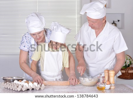 an elderly couple and their grandson knead the dough for the pie together - stock photo