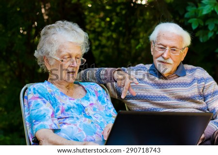 An elderly couple having fun with the laptop in the garden, outside. - stock photo