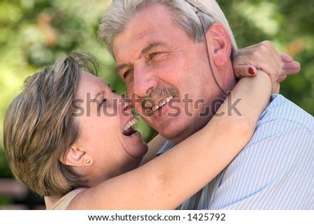 An elderly couple lauging a lot. - stock photo