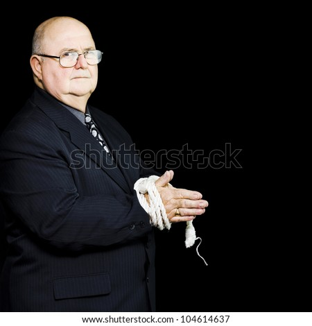 An elderly executive stands with his hands tied by a rope for his own safety looking irritably at the camera as he reaches breaking point due top business stress and overwork - stock photo