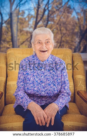 An elderly grandmother laughs - stock photo