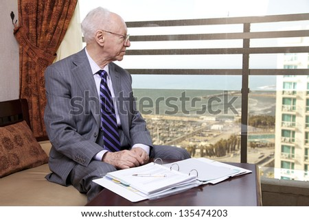 An elderly (in his 80's) business man wearing suit and tie sitting in a hotel's business lounge, looking through the window for a little break from the documents he is inspecting. - stock photo