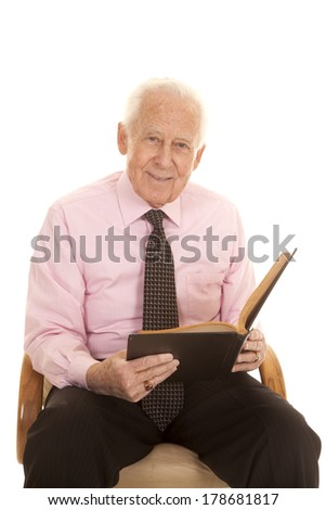 An elderly man  his pink shirt and tie with a smile on his face studying his book. - stock photo