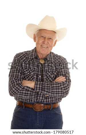 An elderly man in a cowboy hat standing with his arms folded. - stock photo