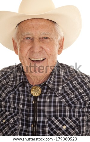 An elderly man in a cowboy hat up close smiling. - stock photo