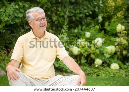 An elderly man is sitting relaxed in a garden while resting his arms on his knees and smiling to the right - stock photo