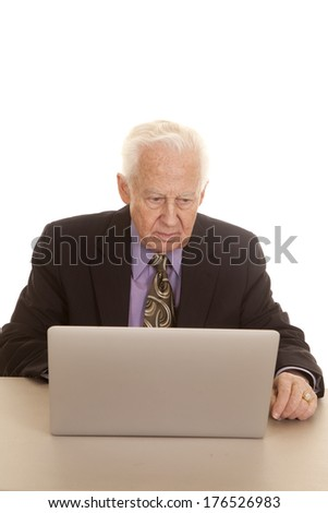 An elderly man sitting at a computer in a suit and tie. - stock photo