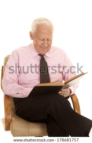 an elderly man with a smile on his face studying a book. - stock photo