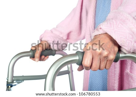 An elderly senior adult using a walker to help her mobility.  Focus is on the hand. - stock photo