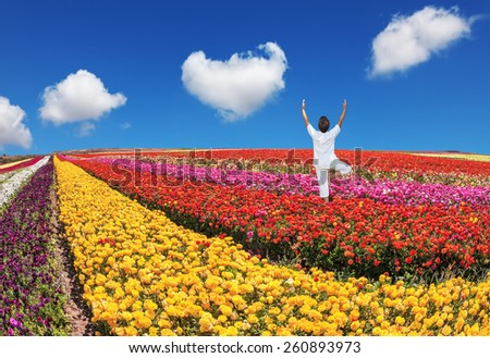 "An elderly woman dressed in white doing yoga pose ""Tree"". Buttercups blooming garden. Farmers field with flowers grown for export sales - stock photo"