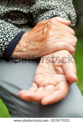 An elderly woman holding her painful wrist - stock photo