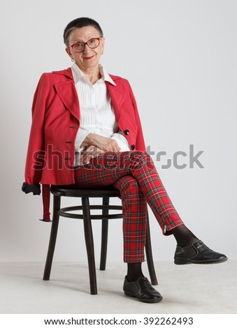 An elderly woman in red glasses sitting on a chair . - stock photo