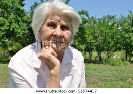 An elderly woman, lost in thought, leaning on the arm, von Garden - stock photo