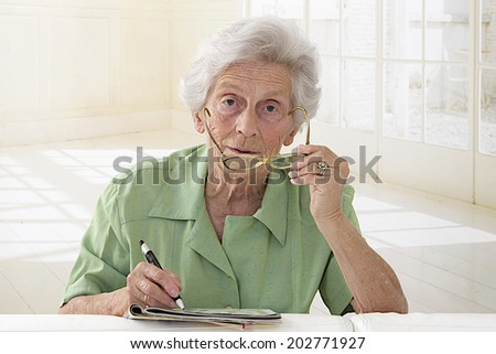 An elderly woman portrait holding glasses and doing crossword - stock photo