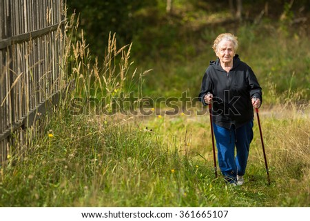 An elderly woman practices Nordic walking in the Park. - stock photo
