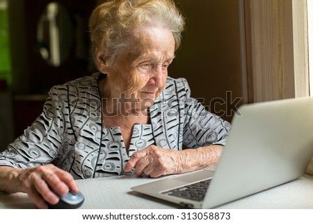 An elderly woman working on a laptop. - stock photo