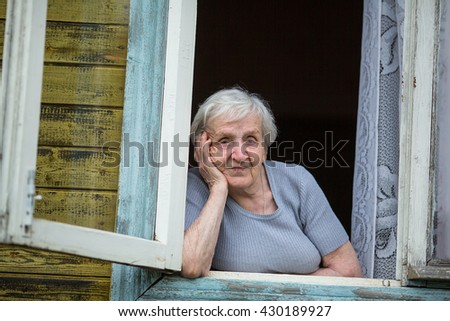An elderly woman (80 years old) sitting and looking out the window. - stock photo