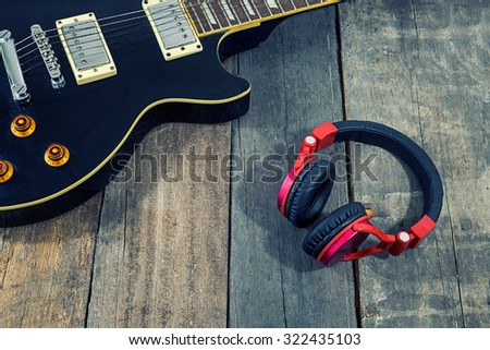 An electric guitar,headphones on a rustic wooden table vintage tone. - stock photo