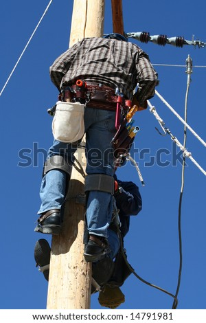 an electrical lineman student working on a pole at a lineman college - stock photo