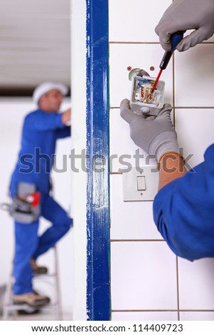 An electrician fixing an outlet. - stock photo