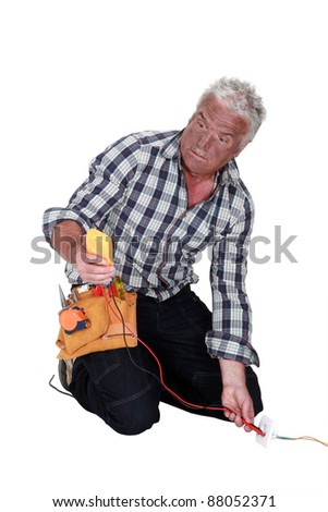An electrocuted tradesman staring at his multimeter - stock photo