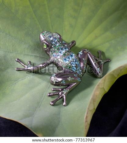 An elegant brooch designed in frog shape on lotus leaf - stock photo
