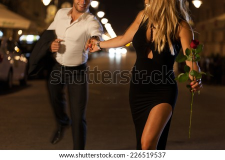 An elegant couple holding hands when running on a date at night - stock photo