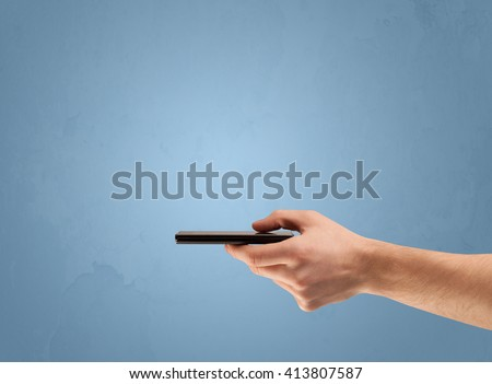 An elegant hand holding mobile phone in front of an empty clear blue wall background concept - stock photo