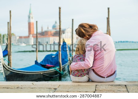 An elegant mother is sitting next to her daughter along the water's edge near St. Mark's Square in Venice. She is hugging her daughter close, resting her head against her daughter's head. - stock photo