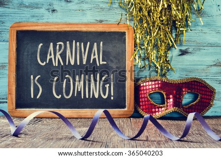 an elegant red and golden mask, a chalkboard with the text carnival is coming and a streamer on a rustic wooden surface - stock photo