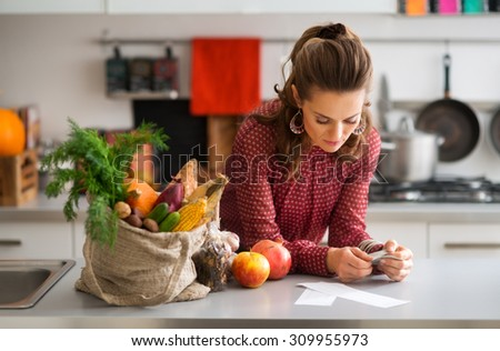 An elegant woman is reading the shopping lists on her kitchen counter. Next to her on the kitchen counter, a burlap sac holds a wide variety of fall fruits and vegetables. - stock photo