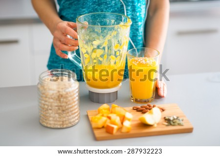 An elegant woman's hand is resting against a blender, which is standing next to a full glass of a freshly-made smoothie. In the foreground, a wooden board with seasonal fruits, nuts, oats, and seeds. - stock photo