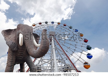 An elephant parading in front of a big colorful ferris wheel on a blue cloudy day. - stock photo