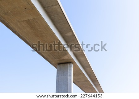 An elevated concrete road bridge seen from below. Supported by a single visible pillar. Blue sky background. - stock photo