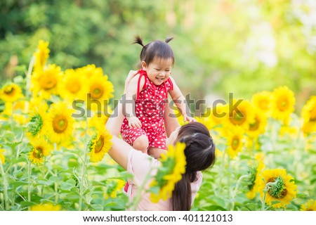 An emotional picture of 1 year old baby and her mother feeling happy together in the sun flower garden. - stock photo