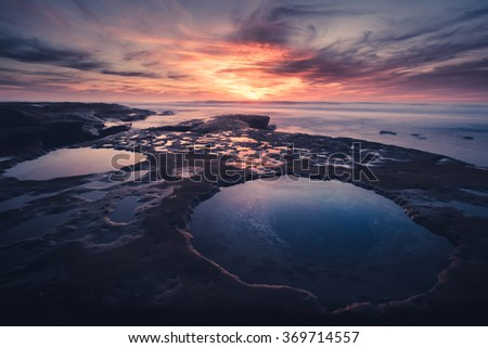 An empty california sunset looking out over tide pools and surf. - stock photo