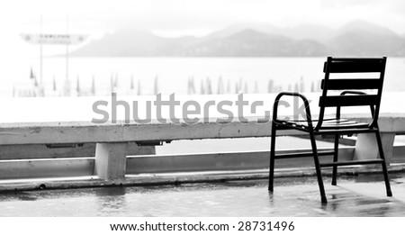 An empty chair on a sidewalk of La Croisette street by the seaside of Cannes - stock photo