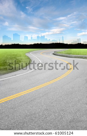 An empty curved road leading off into the horizon of trees and countryside. - stock photo