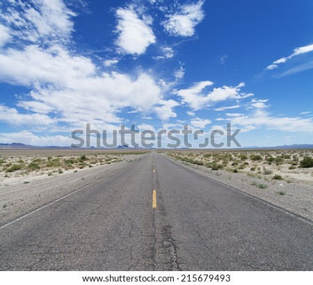 an empty desert road cuts across Nevada to the horizon under a partly cloudy blue sky - stock photo