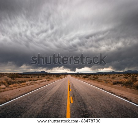 An empty desert road with dark and foreboding storm clouds on the horizon. - stock photo