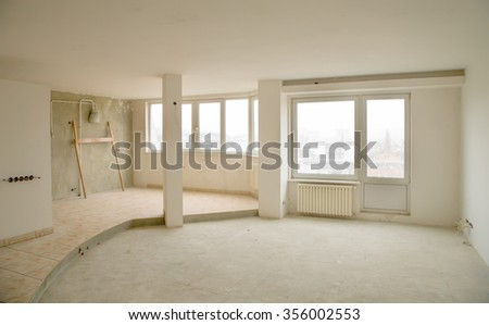 An empty interior of a newly built apartment with white walls and big windows - stock photo