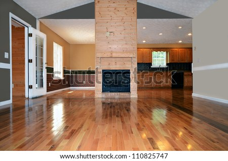 An empty living area with a fireplace.  Behind it is the dining and kitchen area. - stock photo