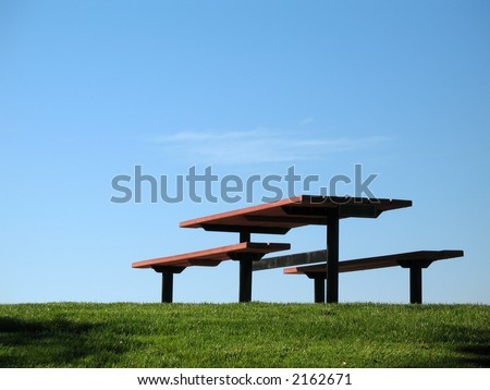 An empty picnic table sits on the green grass and blue sky background - stock photo