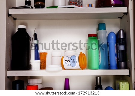 An empty pill bottle with a frowny face lies on a shelf in a medicine cabinet. - stock photo