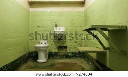 An empty prison cell at Alcatraz National Park with hideous institutional green paint. - stock photo