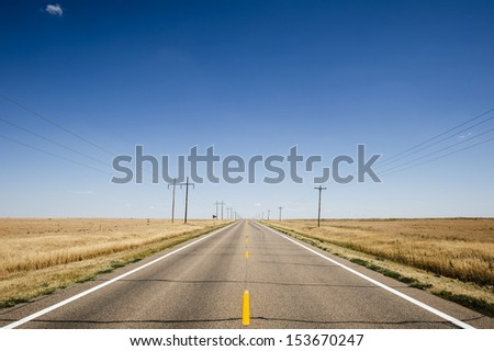 An empty rural highway with blue sky horizon - stock photo