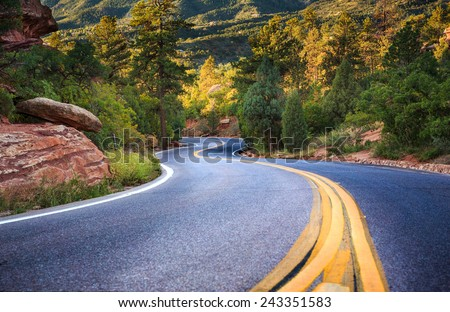 An empty S Curve in a forested road located in the mountains near Colorado Springs in Fall - stock photo