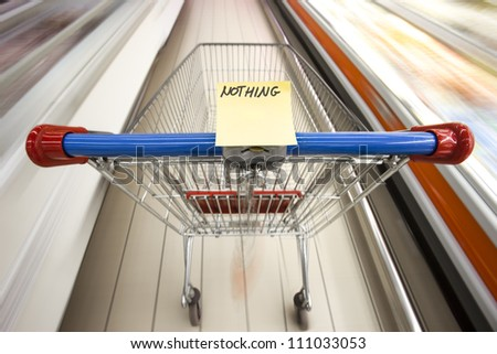 An empty shopping cart in motion in a supermarket - empty shopping list - stock photo